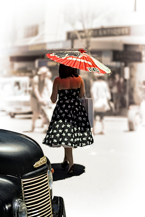 Woman shaded by a parasol on a blazing hot day