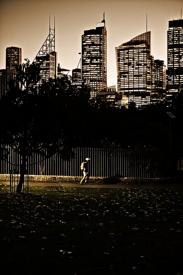 At dusk infront of a city skyline, a skateboarder rides through the park